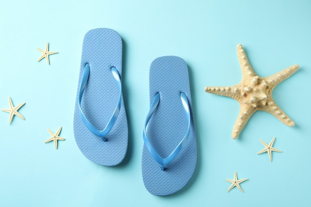Flip flops and sea stars on blue background
