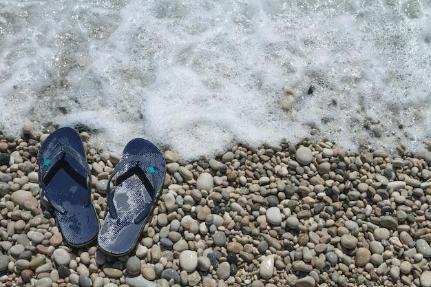 小石のビーチの海岸の波からの泡で海の水に触れるビーチサンダルスリッパ