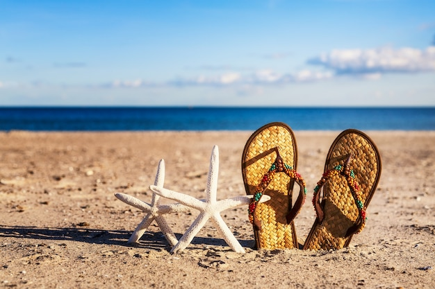 Flip flops and starfish on sand beach. summer vacation on baltic sea, germany concept