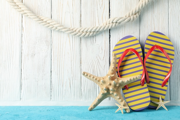 Flip flops and starfishes on white wood, space for text