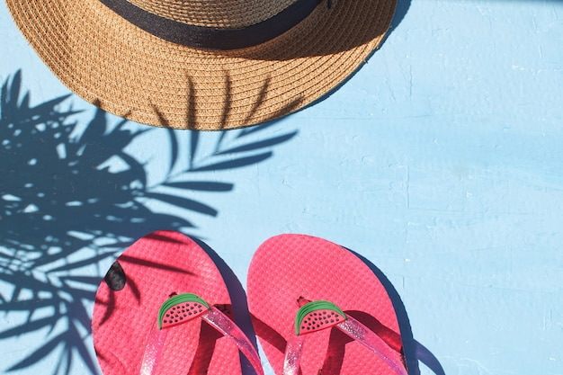Flip flops straw hat light blue background top view copy space tropical leaf shadow