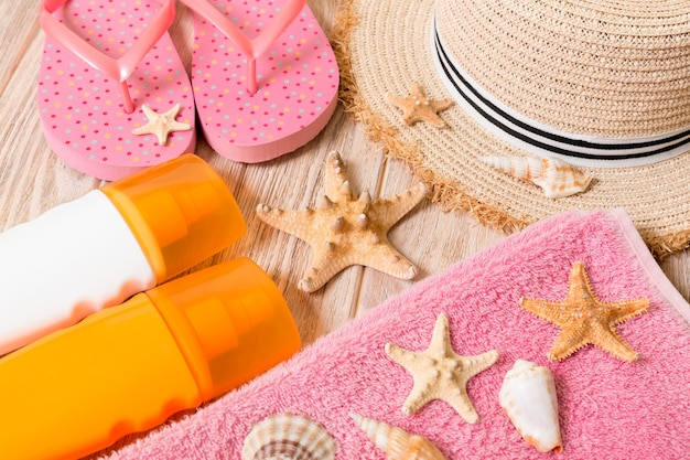 ビーチサンダル、麦わら帽子、ヒトデ、日焼け止めボトル、木製の背景の上面図にボディローションスプレー。フラットレイ夏のビーチの海のアクセサリーの背景、休日のコンセプト。