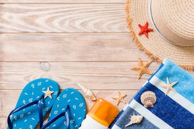 ビーチサンダル、麦わら帽子、ヒトデ、日焼け止めボトル、木製の背景の上面図にボディローションスプレー。フラットレイ夏のビーチの海のアクセサリーの背景、休暇の概念。
