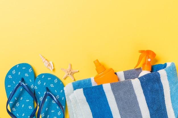 ビーチサンダル、麦わら帽子、ヒトデ、日焼け止めボトル、黄色の背景の上面図にボディローションスプレー。フラットレイ夏のビーチの海のアクセサリーの背景、休日のコンセプト。