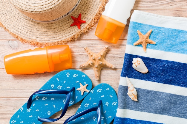 Flip flops, straw hat, starfish, sunscreen bottle, body lotion spray on wooden background top view . flat lay summer beach sea accessories background, holiday concept.