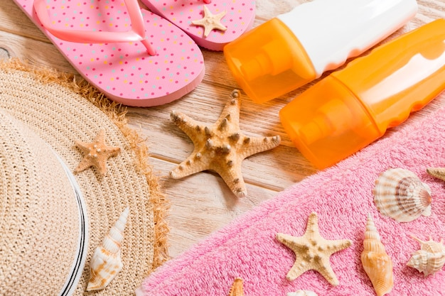 Flip flops, straw hat, starfish, sunscreen bottle, body lotion spray on wooden background top view . flat lay summer beach sea accessories background, vacation concept.