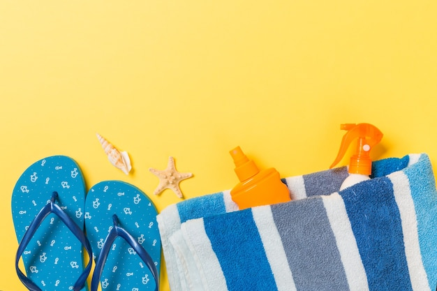 Flip flops, straw hat, starfish, sunscreen bottle, body lotion spray on yellow background top view . flat lay summer beach sea accessories background, holiday concept.