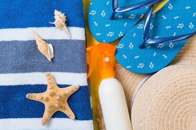 Flip flops, straw hat, starfish, sunscreen bottle, body lotion spray on yellow background top view . flat lay summer beach sea accessories background, vacation concept.