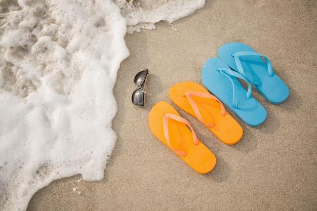 모래에 플립 플롭, 선글라스 및 불가사리