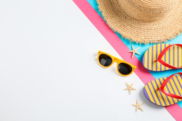 Flip flops, sunglasses, starfishes and straw hat on color table