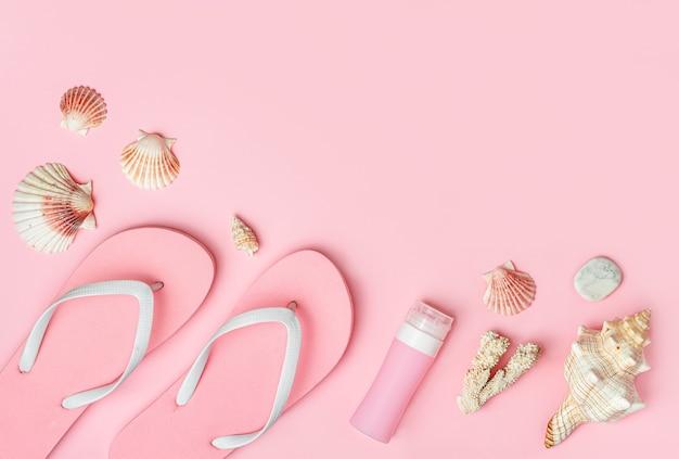 パステル ピンクの背景にフリップフ ロップ、日焼け止めボトル、貝殻、コピー スペース、フラット レイアウト。