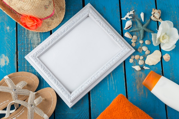 Flip-flops, towel, hat, sun cream, seashells, starfish, orchid and photo frame