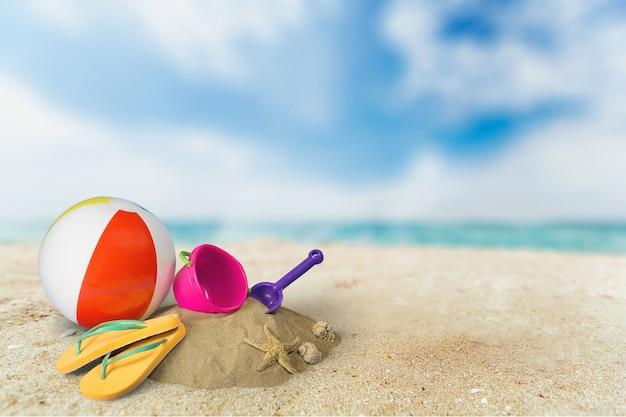 砂浜の海岸でボールとおもちゃのビーチサンダル。旅行のコンセプト
