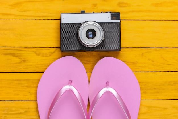 黄色い木製のレトロなカメラでビーチサンダル
