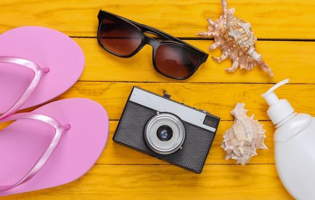 サングラス、カメラ、日焼け止め、黄色い木製の貝殻とビーチサンダル