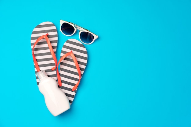 Flip-flops with sunscreen and sunglasses on blue, flat lay