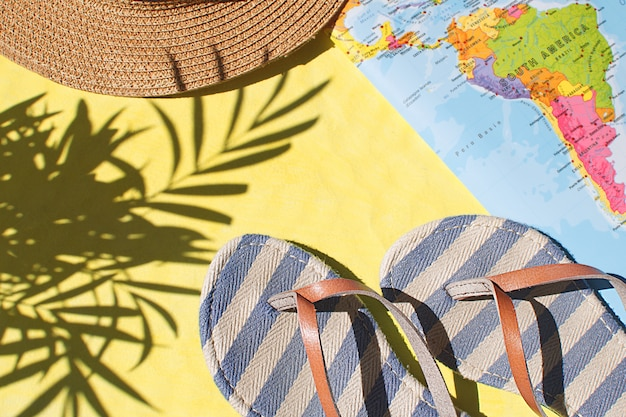 Flip flops, world map and straw hat on yellow background