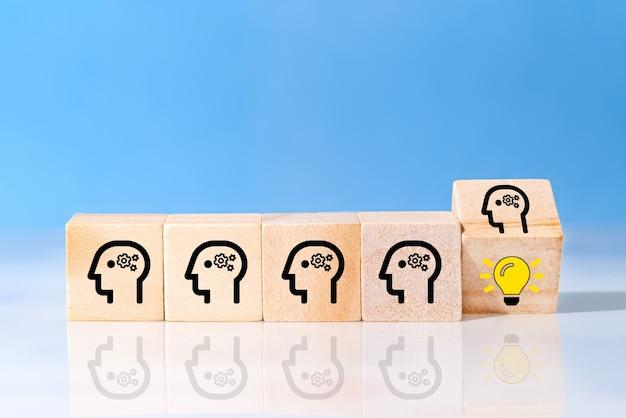 머리 인간의 기호와 아이디어를 드러내는 전구 아이콘으로 나무 큐브 블록을 뒤집습니다. 개념 창의적인 아이디어와 혁신