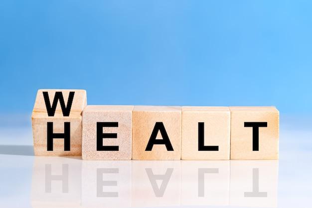 健康に言葉の富を持つ木製の立方体を裏返します。生命保険とヘルスケアの概念への投資