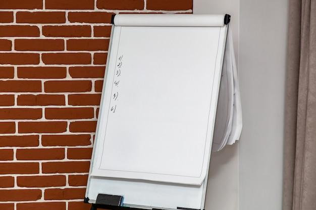 벽돌 벽의 배경에 대해 사무실에 종이와 그려진 숫자가 있는 플립차트. 회의 및 프레젠테이션용 종이가 있는 플립 차트는 발표자에게 도움이 됩니다.