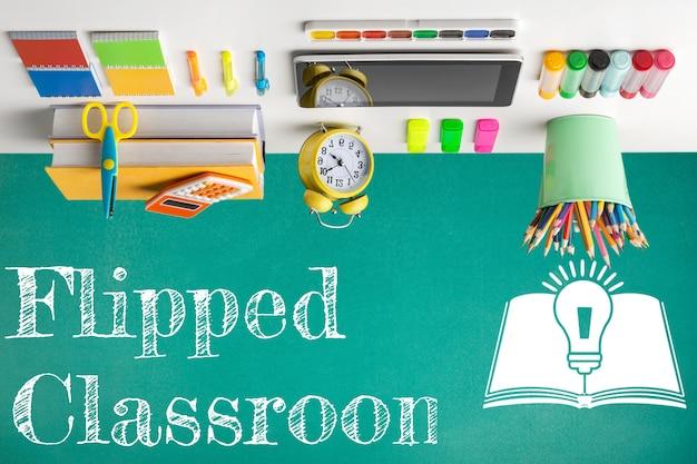 Перевернутая концепция класса на доске с apple и цифровой планшет на деревянном столе