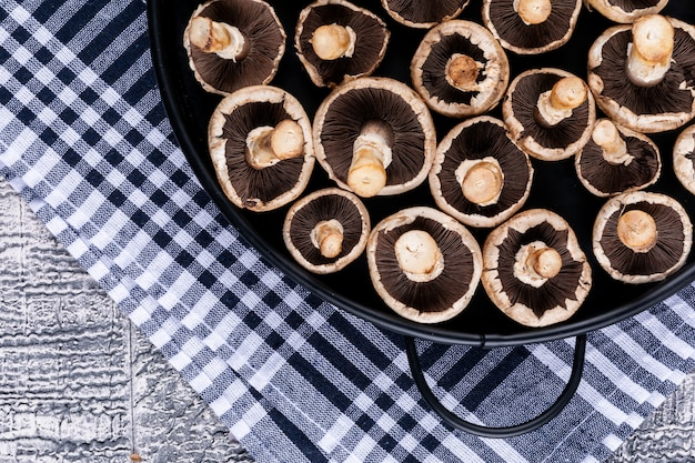 灰色の木製のテーブルにピクニック布の上面に鍋に白いキノコを反転