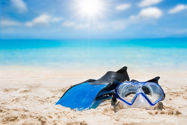 Flipper and snorkel on sand beach with bright sun