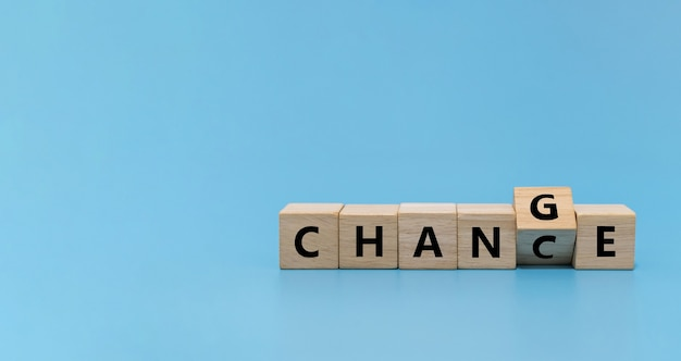 Перелистывание слова изменить на шанс на деревянном кубическом блоке на синем фоне, рыночная тенденция, позитивное мышление, стратегия финансирования бизнеса, запуск бизнеса, интернет-маркетинг, цель и концепция целевого плана