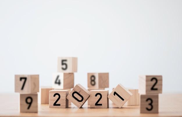 Переворачивание блока деревянных кубиков 2021 года. веселого рождества и счастливого нового года концепции.
