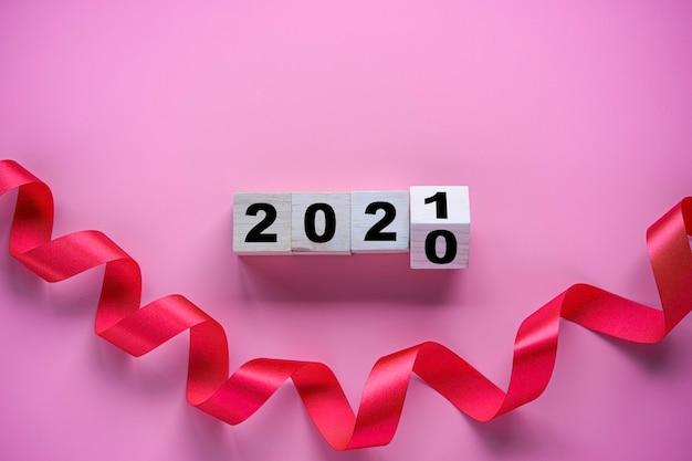 분홍색 배경에 리본으로 2020 년에서 2021 년까지 나무 큐브 블록 뒤집기