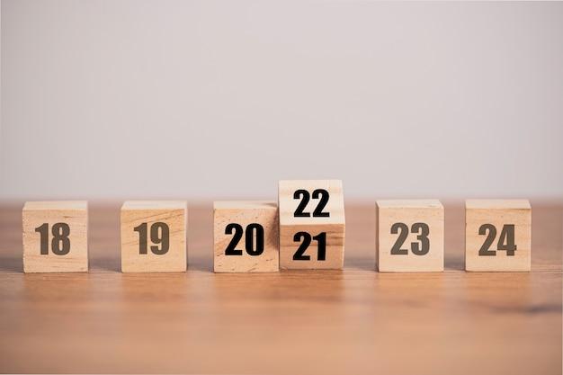 나무 큐브 블록을 뒤집어 2021 년에서 2022 년으로 변경합니다. 기쁜 성 탄과 새 해 복 많이 받으세요 개념입니다.