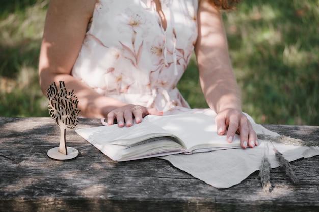 屋外のひびの入った木製のテーブルでノートブックのページをめくる