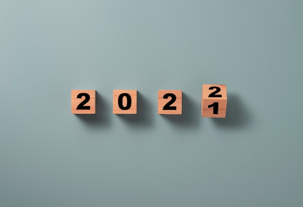 Flipping wooden block cube to change 2021 to 2022 on blue background, merry christmas and happy new year preparation concept.