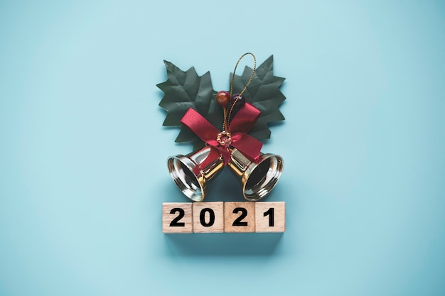 Flipping of wooden cubes block to change 2020 to 2021 year with golden bell on blue background