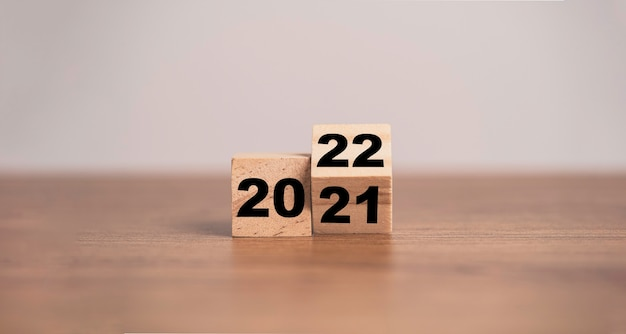 Flipping of wooden cubes block to change 2021 to 2022 year. merry christmas and happy new year concept.
