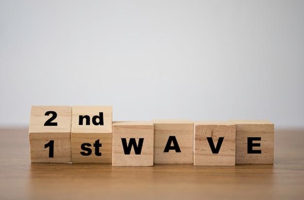 Covid-19コロナウイルスの大流行を予測するために、変化する木製の立方体ブロックを第1波から第2波への変化に合わせてブロックします。