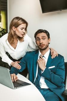 浮気またはセクハラ。ブロンドの女性はラップトップで作業する人を誘惑し、同僚は仕事で浮気します。オフィスで部下を誘惑する
