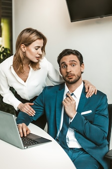 Flirtation or sexual harassment. blonde woman seduces man working with laptop, colleagues flirt at work. seducing a subordinate in office