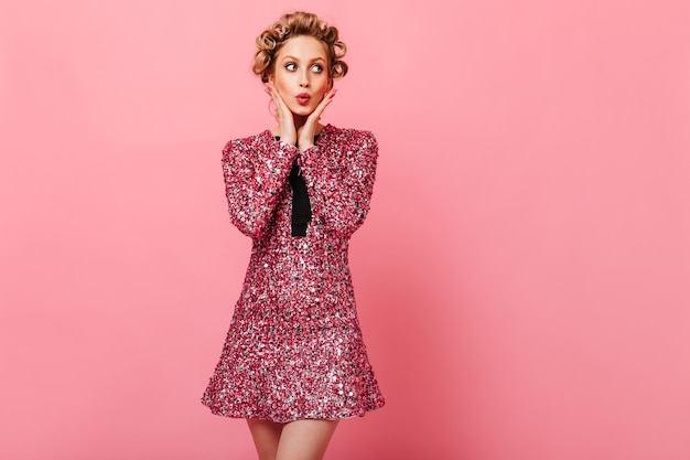 Flirtatious woman in brilliant outfit whistles on pink wall