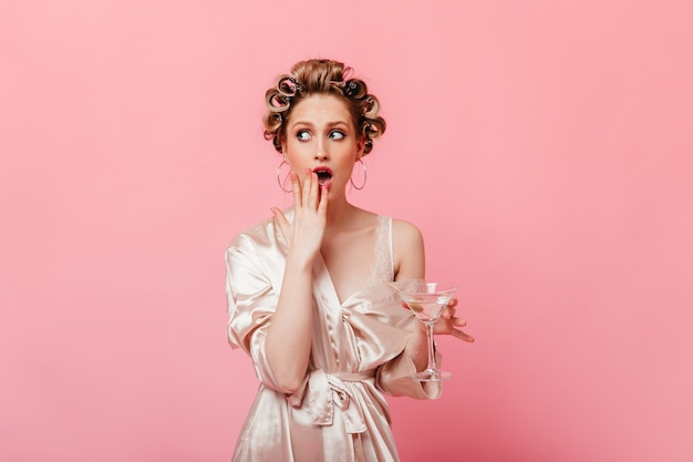 Flirtatious woman in silk robe holding martini glass and covering her mouth in surprise