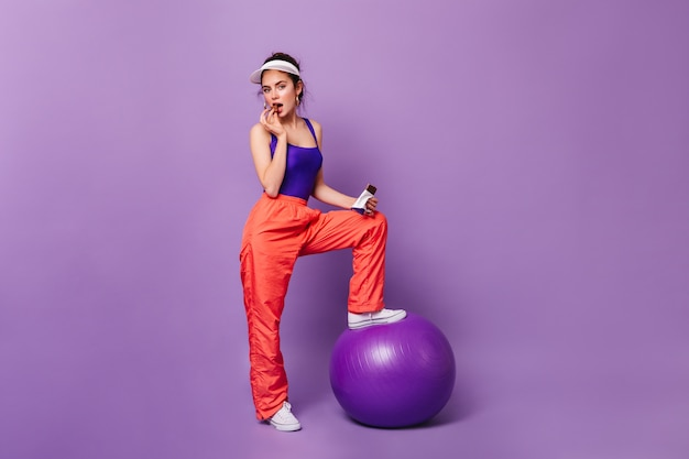 Flirtatious woman in sporty outfit posing on purple wall with fitball