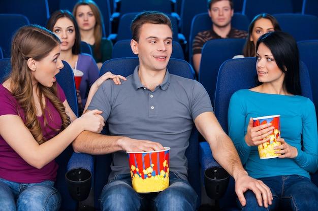 영화관에서 유혹. 젊은 남자는 여자 친구와 함께 앉아서 영화관에서 영화를 보면서 다른 여자 무릎에 손을 잡고