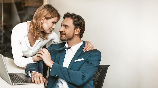직장 커플 유혹. 매력적인 백인 직장인 남자와 여자는 부드럽게보고 서로 만지십시오.