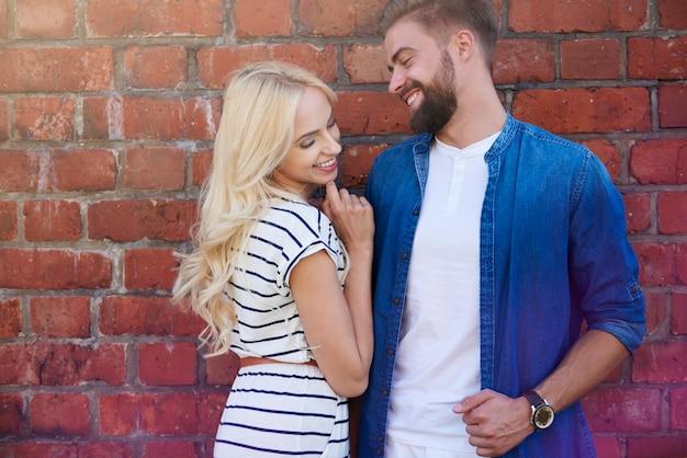 Flirting next to a brick wall