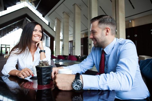 カフェでいちゃつく。コーヒーと会話を楽しんでいるカフェに座っている美しい愛情のあるカップル。愛とロマンス。