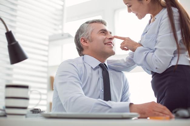사무실에서 유혹. 그의 동료를보고 그녀와 유혹하는 동안 웃고 행복 좋은 잘 생긴 남자