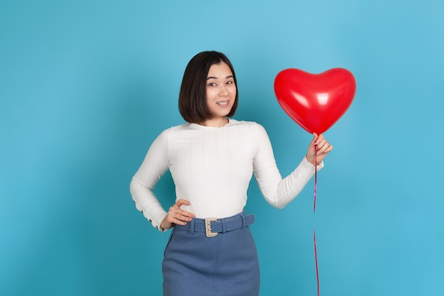 Flirting, mischievous young asian woman holds a heart-shaped flying balloon