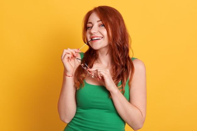 Флиртующая улыбающаяся женщина кусает оправу своих очков и в повседневной одежде
