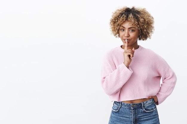 金髪のヘアカットが官能的に見える軽薄なアフリカ系アメリカ人の女性は、腰に手をつないで、口に人差し指を持って、秘密を隠したり、驚きを作ったりして、わずかなロマンチックな笑い声でshhジェスチャーを示しています