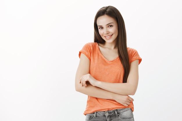 Кокетливая и кокетливая привлекательная женщина позирует и улыбается